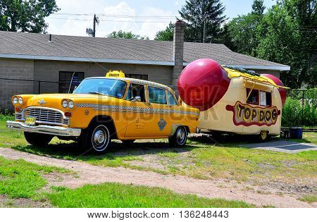 Middletown CT - July 9 2013: Vintage yellow NYC checker taxi with hot dog truck on wheels parked in a yard *