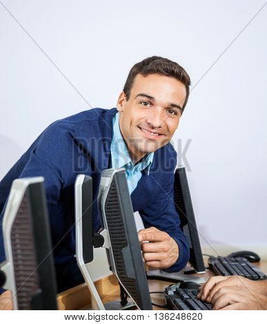 Portrait Of Happy Teacher Assisting Senior Student At Computer D