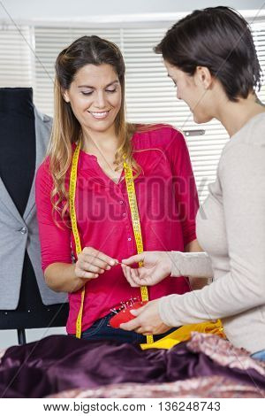 Tailor Giving Pin To Colleague In Factory