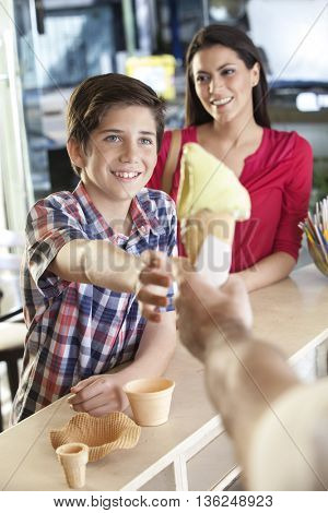 Boy Receiving Vanilla Ice Cream Cone From Seller By Mother