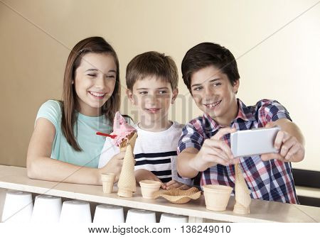 Preteen Boy Taking Selfie With Siblings Through Smart Phone