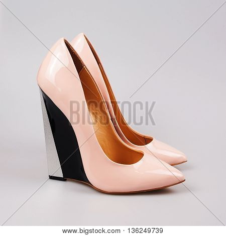 Female pink high heeled shoes over grey