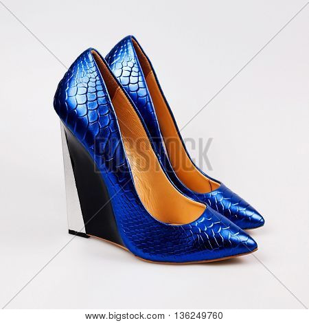 Female blue high heeled shoes over white