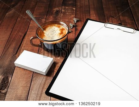 Close-up of blank branding template on vintage wooden table background. Blank Letterhead coffee cup and business cards. Photo of blank stationery. Responsive design mockup.