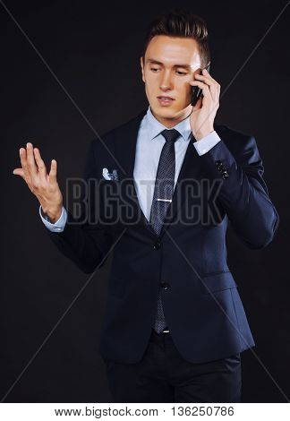young pretty business man standing on black background, modern hairstyle, talking on phone emotional, wearing sunglasses
