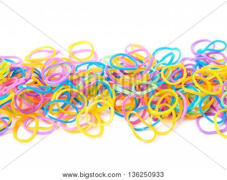 Surface covered with multiple colorful resin loom bands over the white background