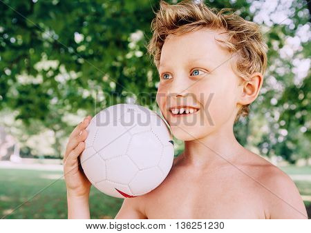 Boy with ball portrait in summer park