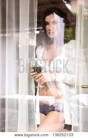 A beautiful young woman standing in the window in underwear and enjoying a glass of wine.