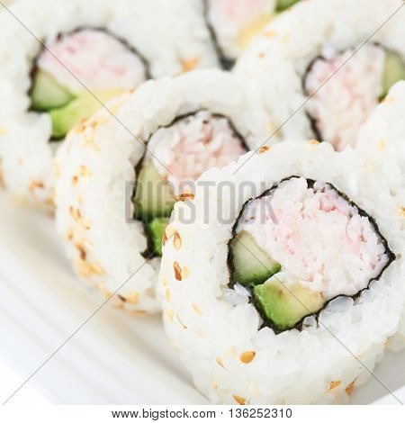 Set of sushi rolls served in a delivery container package, close-up crop shot composition