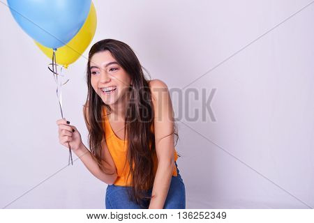 Happy young woman holding balloons. Caucasian beautiful woman isolated over grey background.
