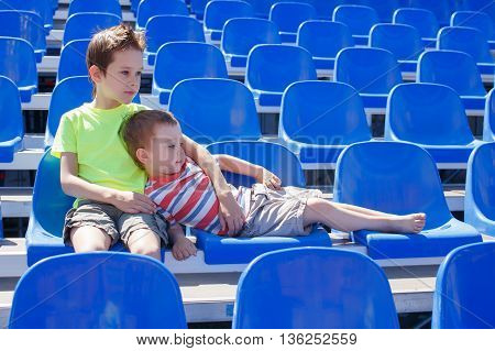 younger sport fans. the two boys took their seats in the stadium and waiting patiently when the game starts or competition