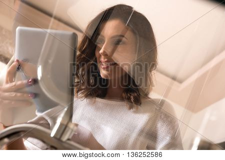 A beautiful young woman sitting at a glass table and using a tablet.