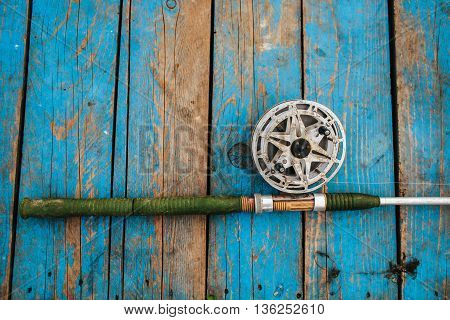 fishing rods lay on the pier near the water