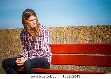 Man Long Hair Sitting On Bench Outdoor