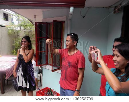 CEBU CITY, CEBU / PHILIPPINES - JULY 29, 2011: People use their cellular telephones to take photographs outside of a home in Cebu City.