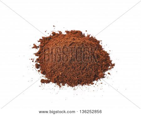 Pile of the ground coffee flakes isolated over the white background