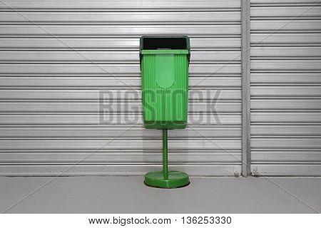 Green Plastic Public Trash Can at Pole
