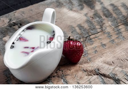 Yogurt with strawberry slices and blueberries on a wooden board - near the yogurt is tasty strawberries