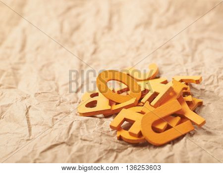 Pile of orange wooden letters over the crumbled paper surface as a backdrop composition