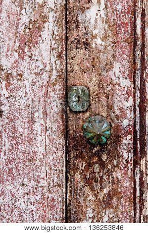 Old grungy wooden door with peeling paint and round door-handle