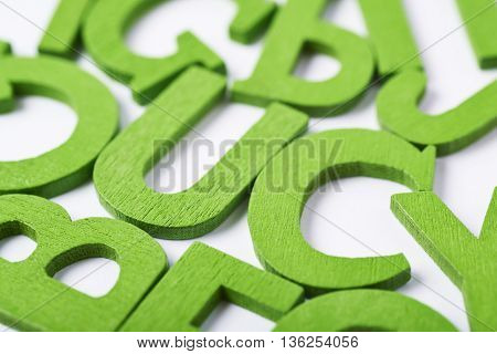 White surface covered with the multiple colorful painted wooden letters as a backdrop composition in green