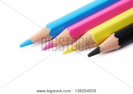 Four cmyk colored drawing pencils composition isolated over the white background, close-up crop