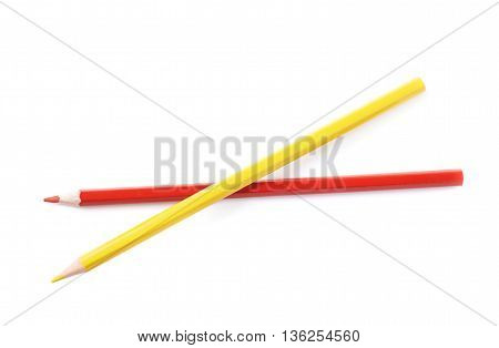 Two red and yellow colored drawing pencils composition isolated over the white background