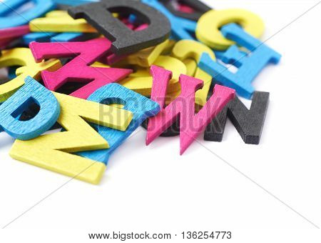 Pile of cmyk painted wooden letters isolated over the white background