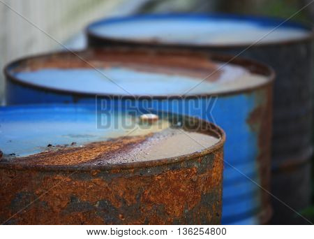 the Row of rusty barrels close to