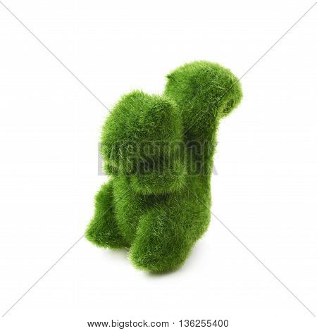Squirrel toy statuette made of plastic green grass as a Easter day decoration isolated over the white background