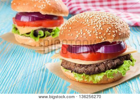 Two homemade cheeseburgers with beef patties and fresh salad on seasame buns, sered on blue wooden table.