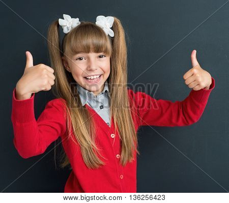 Happy girl showing thumbs up gesture in front of a big chalkboard. Back to school concept.