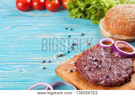 The raw ingredients for the homemade burger on blue wooden table.