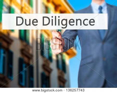 Due Diligence - Businessman Hand Holding Sign