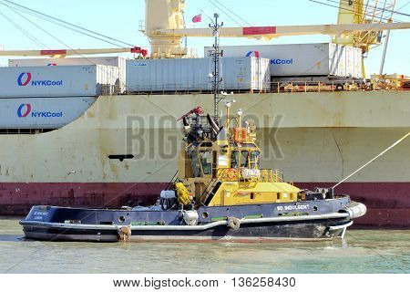 PORTSMOUTH ENGLAND MAY 29 2016: Tugboat SD Indulgent alongside a container ship