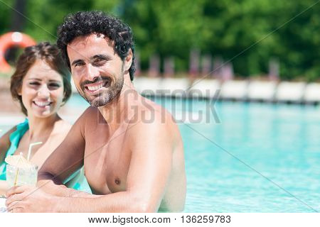 Young couple drinking a cocktail on the poolside
