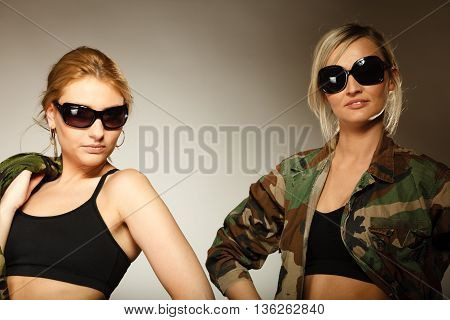 two sexy women in military clothes army girls on gray