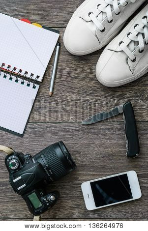 Outfit of traveler or student. Overhead of essentials for modern young person. Different objects on wooden background.