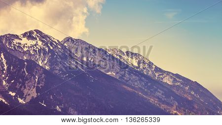 Vintage style looking view to rock snowbound alps mountains summits in clouds