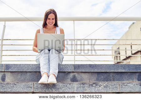 Young beautiful woman with dark hair is sitting outdoors on street stairs working on her notebook computer on a sunny summer day