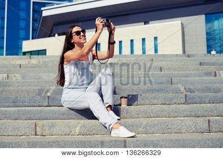 Charming young woman with dark hair in overalls is sitting on the stairs and taking a photo against city view