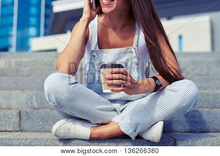 Close-up of young stylish woman sitting with crossed legs and talking on the phone with a cup of coffee in her hands