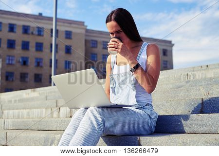 Beautiful woman in casual clothes is drinking coffee and holding laptop on her knees against city view background