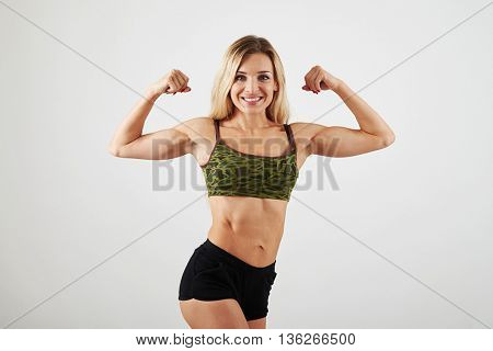 Sexy sporty blonde in khaki sport top and black shorts is showing her muscles and abs isolated over white background