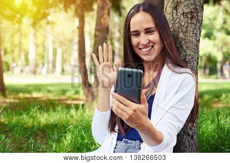 Smiling beautiful lady is resting under tree in park and conducting a video call