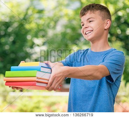 Outdoor portrait of happy teen boy 12-14 year old with books. Back to school concept.