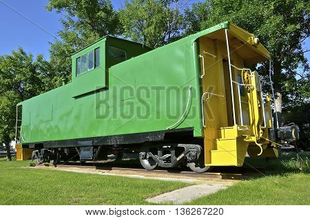 Vintage green caboose with  yellow steps leading to the back door.