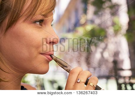 Young woman having fun and relaxing outdoors smoking electronic cigarette e-cig. Closeup of face and copy space