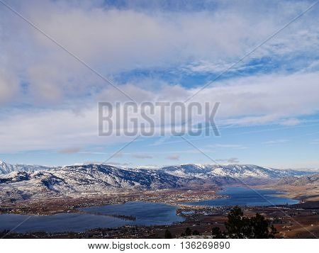 Little village by lake surrounded by snow capped mountains.  Winter in Osoyoos Ocanagan Valley British Columbia Canada.