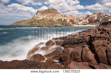 Slow shutter image of waves crashing onto rocks at Castelsardo on the coast of Sardinia in Italy with rocks in the foreground and blue skies and fluffy clouds